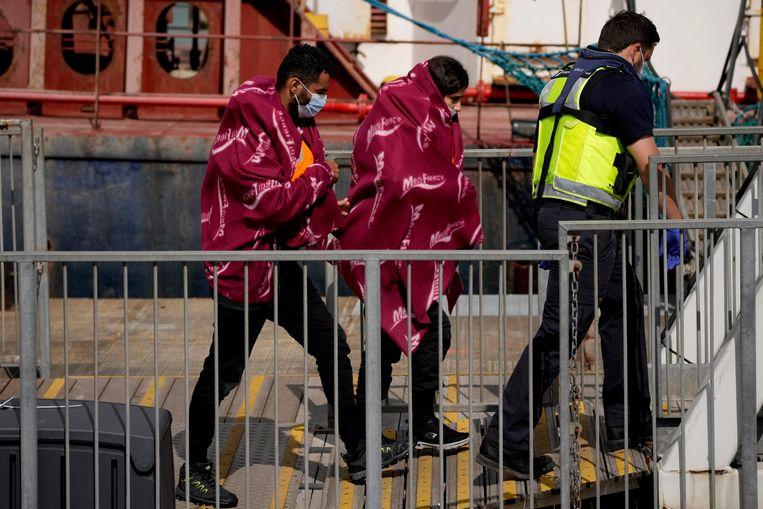 De Britse douane begeleidt twee mensen die per boot uit Frankrijk probeerden over te steken en opgepikt werden. Beeld AP