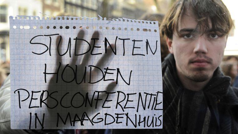 Een betoger uit zijn ongenoegen voor het raam van het Maagdenhuis, waar de persconferentie werd gehouden Beeld ANP