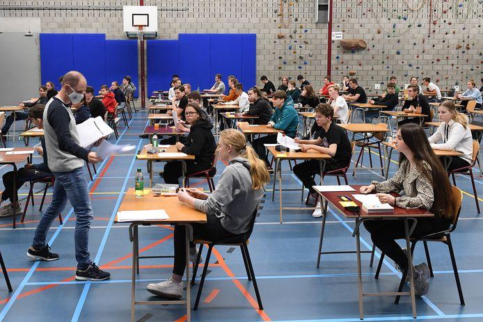 Een medewerker deelt examens uit in de gymzaal van Metameer in Stevensbeek. Leerlingen maakten er maandagmiddag de examens Nederlands en Wiskunde.