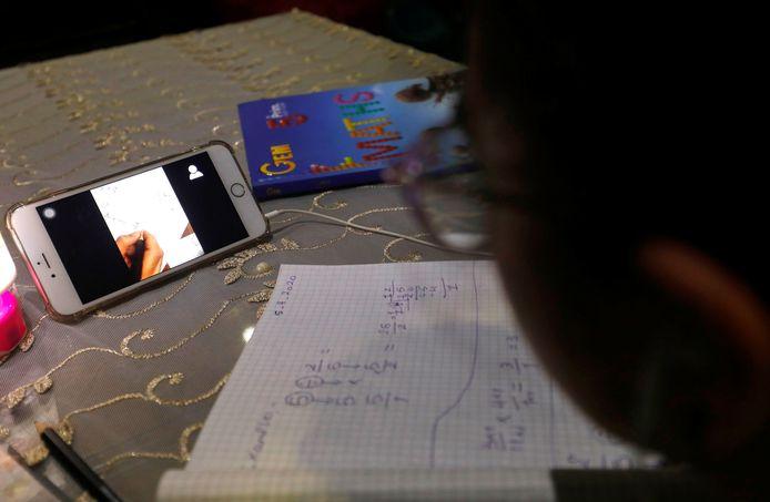 Een student in de Egyptische hoofdstad Caïro volgt wiskundeles via de Zoom-app op zijn iPhone.