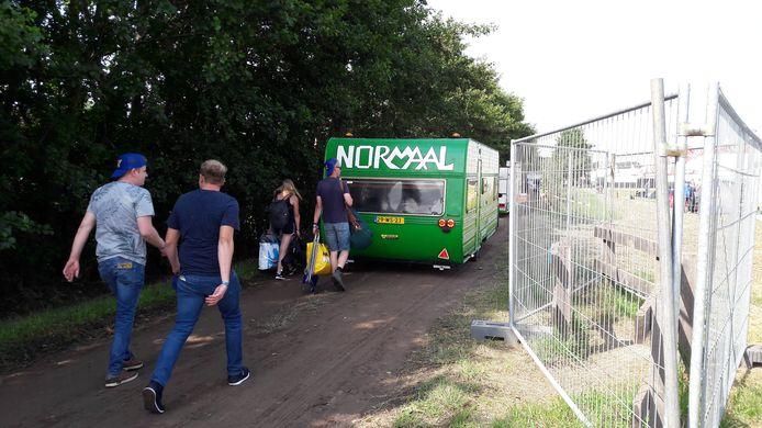 Mensen lopen richting de camping achter een caravan