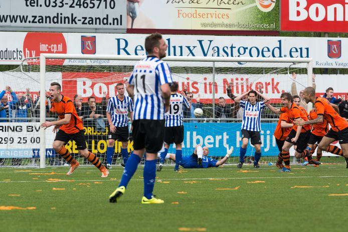 Tim Muller (links) loopt juichend weg, nadat hij in de 96ste minuut voor de gelijkmaker (3-3) zorgt tegen Quick Boys dat met de Nijkerkers de koppositie deelt in de hoofdklasse. Een week later wordt Sparta Nijkerk kampioen.
