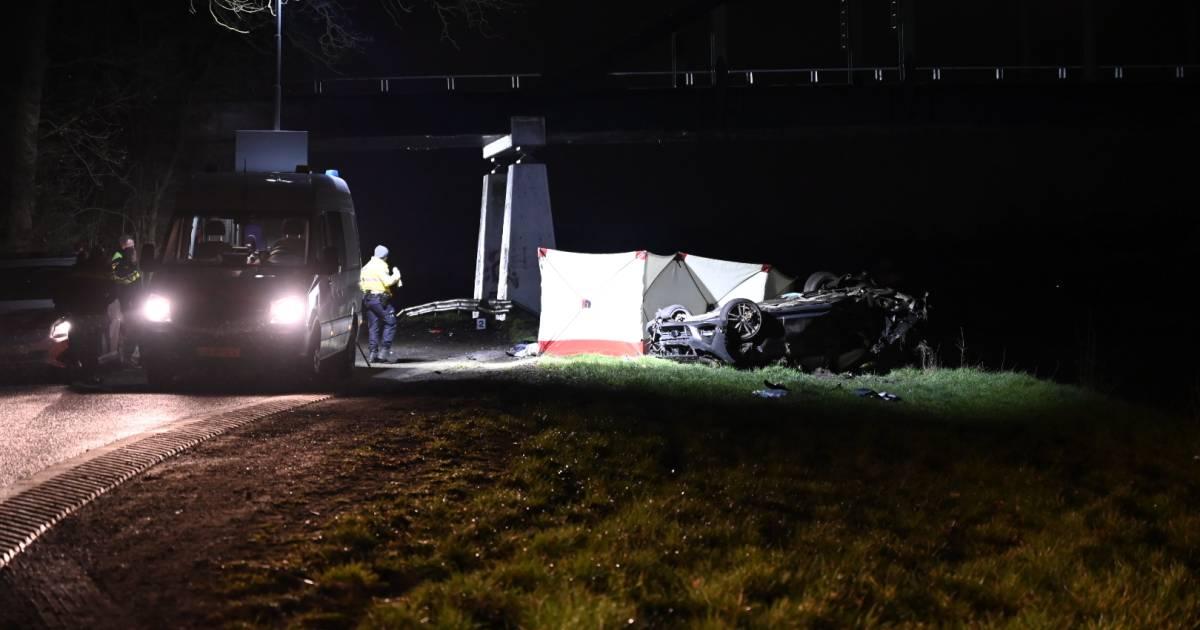 Zwaar ongeluk in Almelo: auto raakt pijler van brug en belandt op z'n kop langs kanaal.