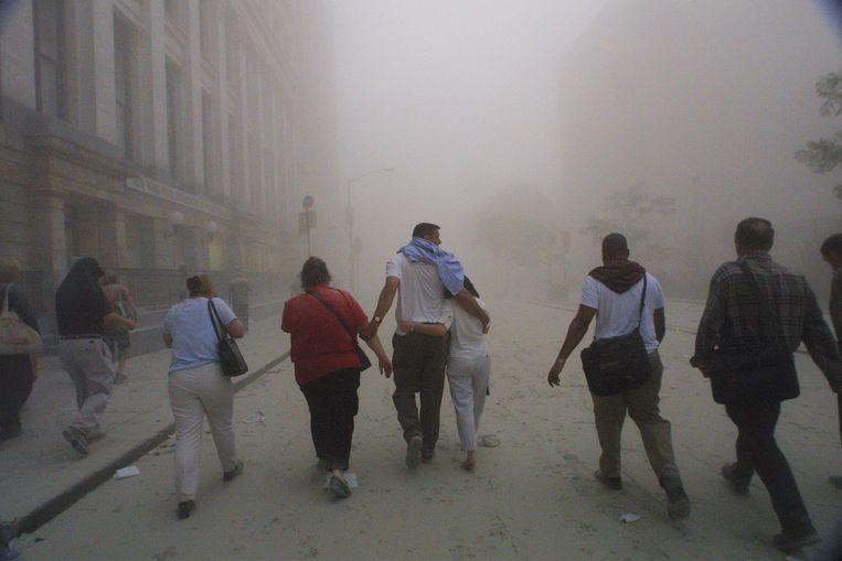 Mensen vluchten weg van het World Trade Center op 11 september 2001.  Beeld Getty