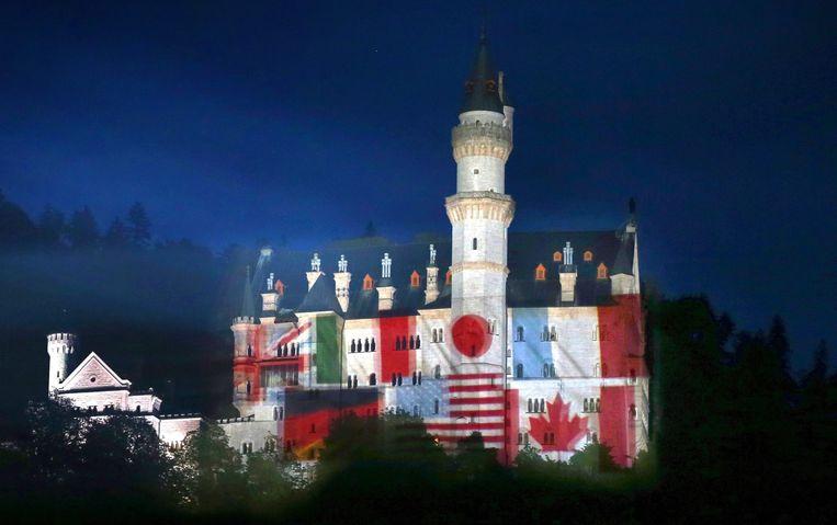 De vlaggen van de industrielanden geprojecteerd op slot Neuschwanstein.