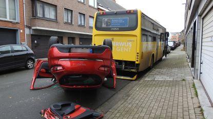 Wagen vliegt over de kop in woonwijk en komt tot stilstand tegen bus