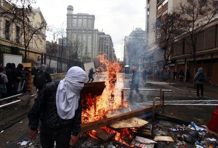 Demonstranten hebben een blokkade opgeworpen op straat in Santiago. Beeld ap