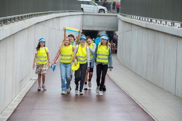 Kinderen stappen de tunnel in.