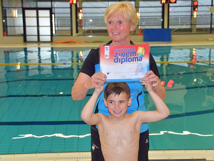 Zwemjuf Nora van der Veeke reikt haar allerlaatste diploma A uit aan haar kleinzoon Boaz.
