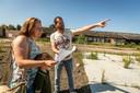 Orinda Brouwer, Patrick Panhuijzen en zoontje Vins lopen met een plattegrond over de oude werf van Adriaans in Stiphout en oriënteren zich op de nieuwe huizen die er komen.