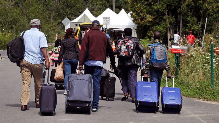 Een Haitiaanse familie loopt met al hun bezittingen in koffers naar een tent in het Canadese Saint-Bernard-de-Lacolle. Beeld ap