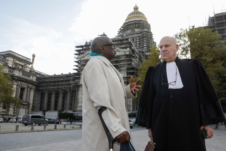 De Rwandees Fabien Neretsé (r.), die deze week terechtstaat in Brussel voor betrokkenheid bij oorlogs- en genocidemisdaden, zijn advocaat.  Beeld BELGA