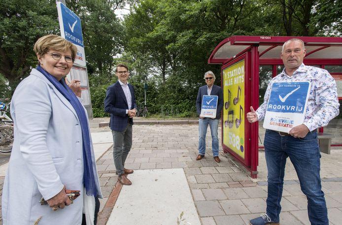 Buschauffeurs Richard Roolvink (rechts) en Marc Hinskens (achteraan rechts), beiden met bord voor zich, zijn samen met de wethouders Anja Prins (links) en Jaimy van Essen aanwezig.