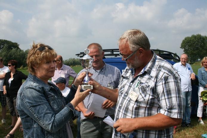 Voorzitter Henny Roos-te Raa van wagenbouwgroep 't Kip krijgt de beker van juryvoorzitter Ben Hasselo van het bloemencorso. Midden achter Henk Bos. Foto Peter Zandee