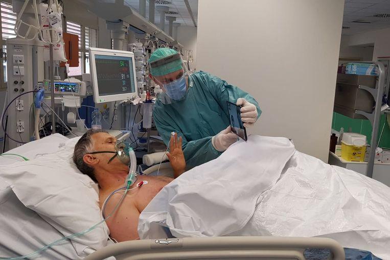 De ernstig zieke coronapatiënt Sergio Faustini praat met zijn familie via een videochat.Een dokter biedt assistentie. Beeld RV Spedali Civili di Brescia