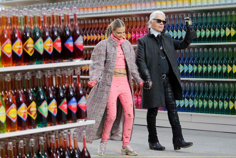 Designer Karl Lagerfeld met model Cara Delevingne aan het einde van de herfst-wintercollectie 2014/2015 in Grand Palais, Parijs, dat omgebouwd is tot supermarkt.