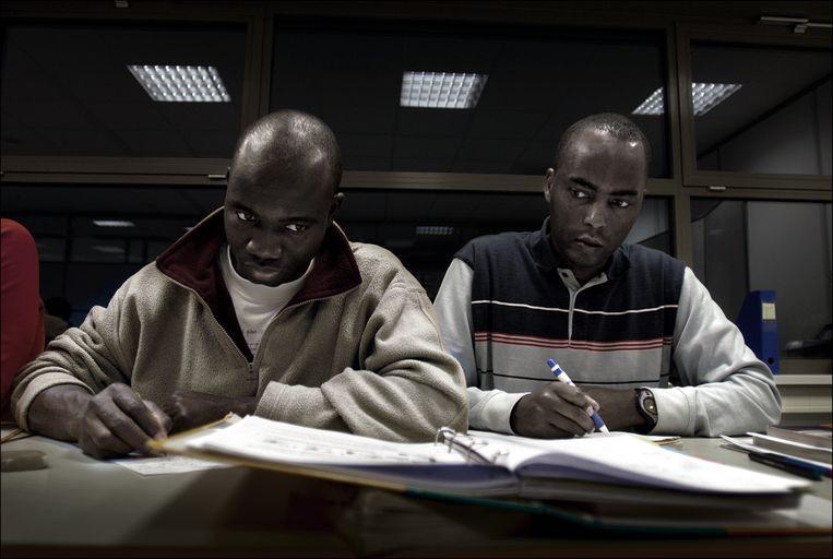 Twee cursisten tijdens de taalles. Beeld Joost van den Broek