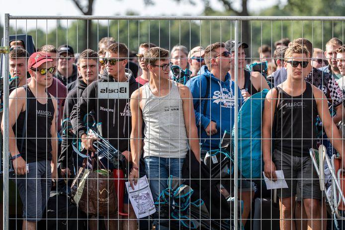 Mensen staan te wachten voor de hekken.