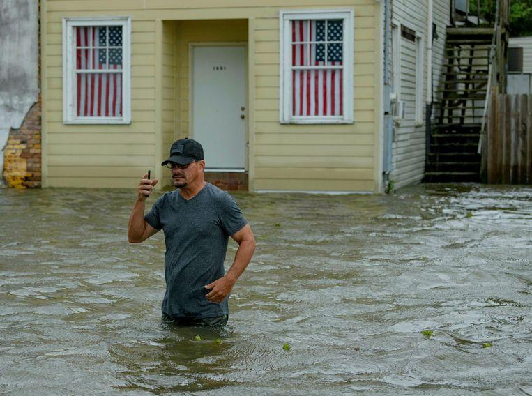 Een man waadt door de overstroomde straten van Mandeville, Louisiana. Beeld AP