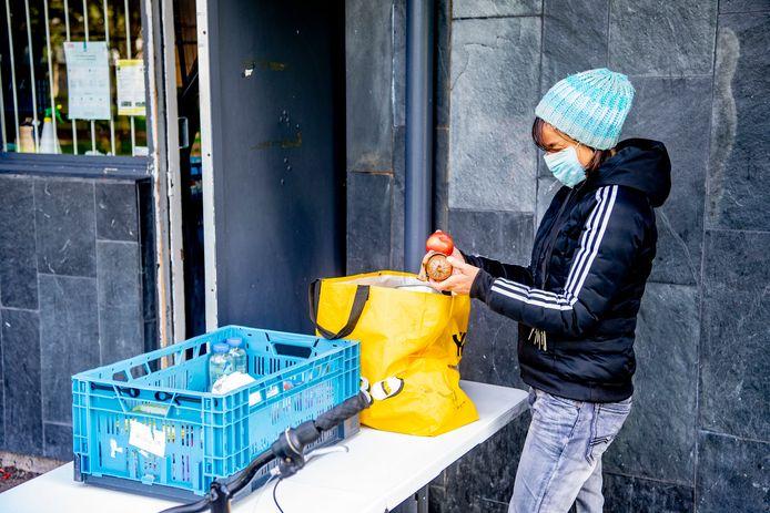 Een mevrouw draagt een mondkapje terwijl ze haar voedselpakket ophaalt. Foto ter illustratie.