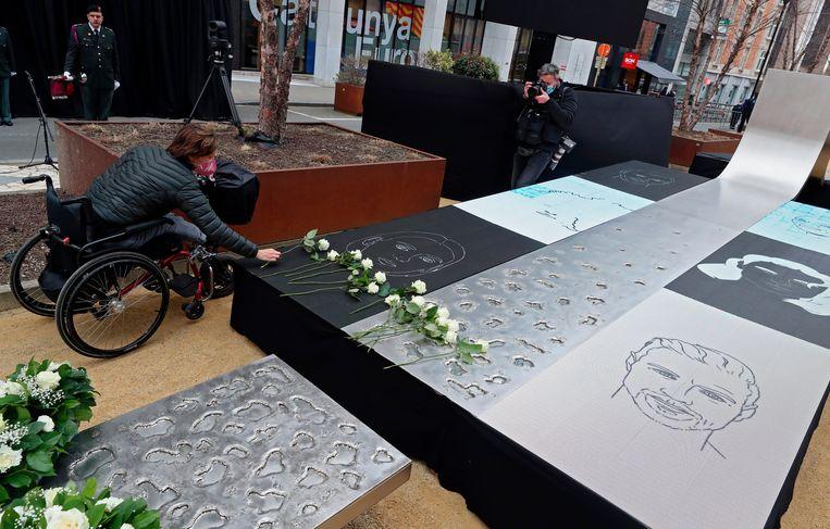 Slachtoffers en familieleden van slachtoffers leggen witte rozen op het monument voor de slachtoffers van de aanslagen op 22 maart in Brussel. Beeld Photo News