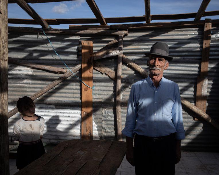 José Emidio dos Reis poseert voor de foto met een van zijn kleinkinder in zijn 'huis'. Het dak is weggewaaid.  Beeld Gonçalo Fonseca