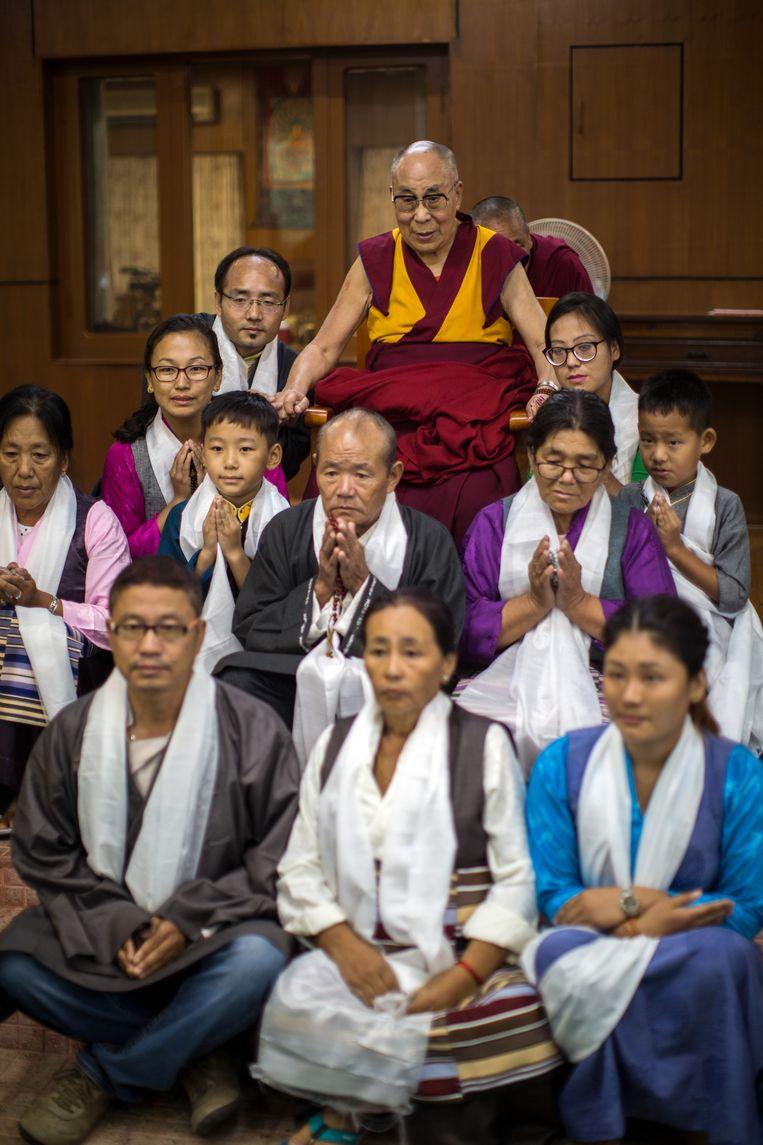 De 14de Dalai Lama, Tenzin Gyatso, tezamen met een groep boeddhisten in het klooster waar de Dalai Lama al bijna 60 jaar  in ballingschap leeft. Beeld Julius Schrank