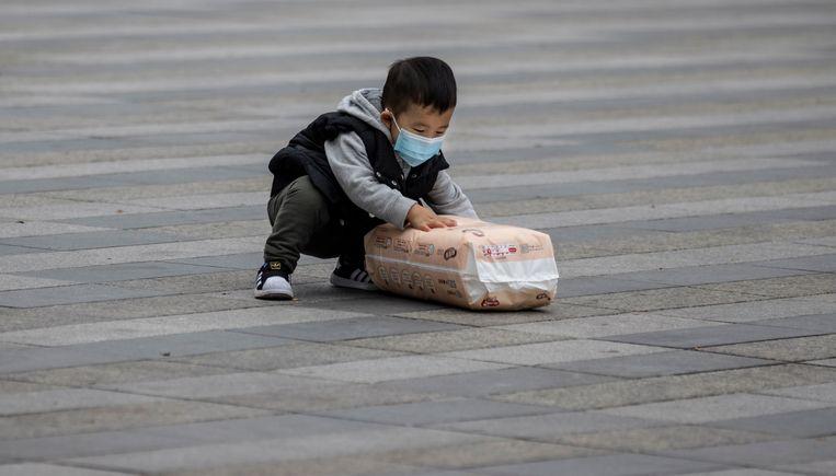 Een Chinees jongetje met een masker in Guangzhou. Beeld EPA