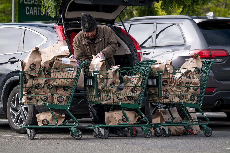 Een medewerker van supermarkt Whole Foods  laadt boodschappen in. Het personeel eist mondkapjes en een regeling voor ziekteverlof. Beeld Bloomberg via Getty Images