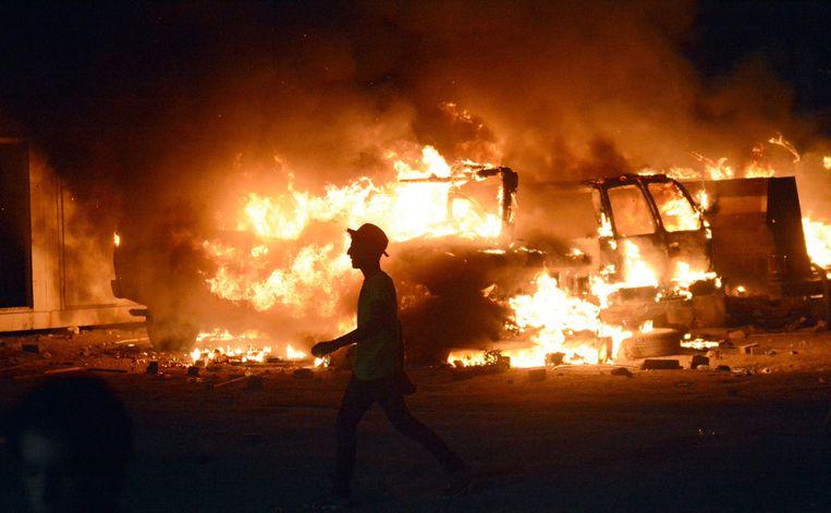 Een demonstrant loopt langs de brandende resten van uitgebrande trucks in Basra.  Beeld EPA
