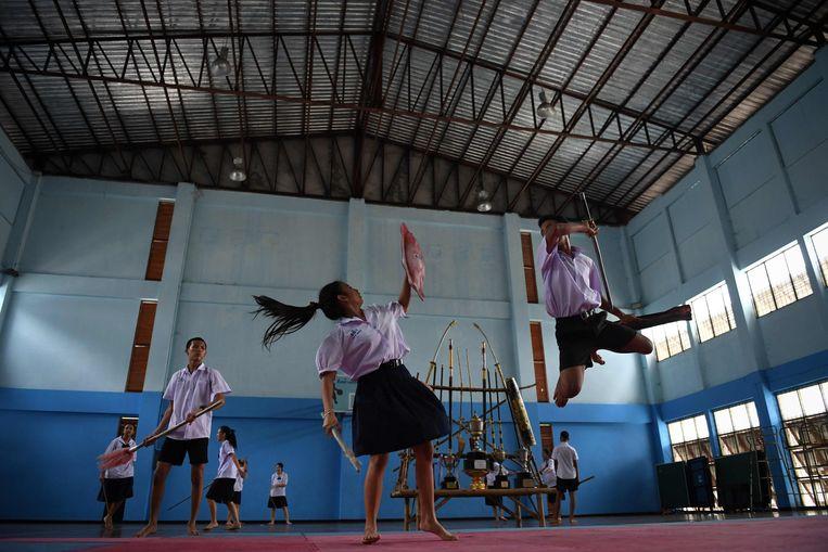 De leerlinge van een school in een buitenwijk van Bangkok weert met haar schild razendsnel een stokslag af van een mede-student. De scholieren oefenen het Krabi Krabong, een vechtkunst die wordt beschouwd als  eerbetoon aan Thaise zwaardvecht-traditie.  Beeld AFP