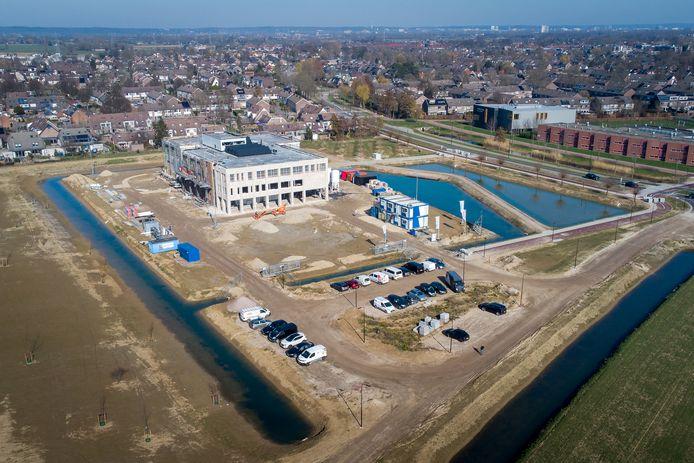 De nieuwbouw van het Overbetuwe College (OBC) aan de Bussel in Elst vordert gestaag. Het dak zit er op en het hele gebouw is inmiddels wind-en waterdicht. Op deze luchtopname is ook goed te zien dat het nieuwe gebouw op een eilandje staat.