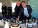 Wethouder Ro van Doesburg (rechts) zet samen met kunstenaar Hans van Lunteren het mes in een taart met daarop de rotonde.