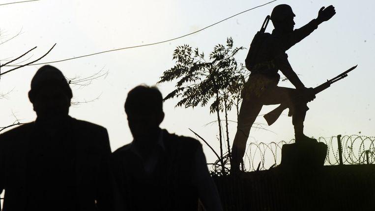 Voetgangers lopen langs een beeld van een soldaat nabij de hoofdstad Islamabad. Beeld afp