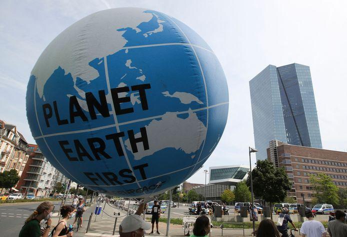 Des militants pour le climat lors d'une manifestation organisée par diverses organisations, dont Greenpeace, pour protester contre les investissements des banques dans les combustibles fossiles, le 13 août 2021 près du siège de la Banque centrale européenne (BCE) à Francfort.