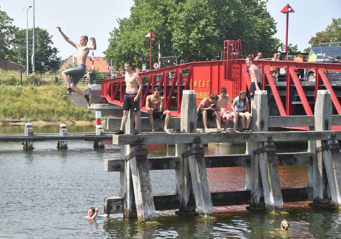 Jongeren nemen een duik vanaf de Draaibrug bij Oost-Souburg.