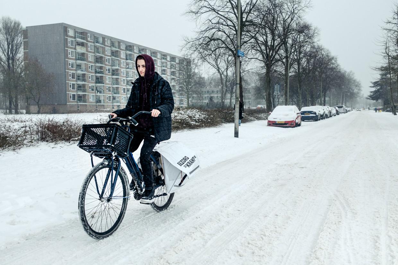 Krantenbezorger Jesse Deppe trotseert het winterweer. Beeld Jakob van Vliet