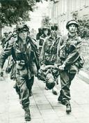 Uitgeputte Britten lopen met een brancard met een  zwaar gewonde kameraad door de Van Oldenbarneveldtstraat in Arnhem. Beeld van de Slag om Arnhem nadat de Britten de strijd rond de oprit bij de Rijnbrug op moesten geven.