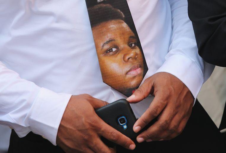 De vader van Michael Brown draagt tijdens de begrafenis een stropdas met het portret van zijn zoon. Beeld getty