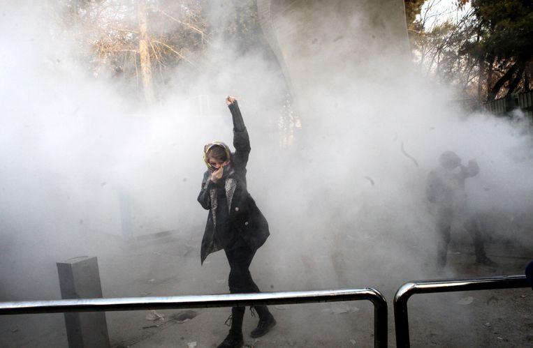 Een Iraanse studente beschermt haar gezicht tegen het traangas dat de oproerpolitie verspreidt. De foto werd 30 december gemaakt, maar de protesten gaan nog steeds door.