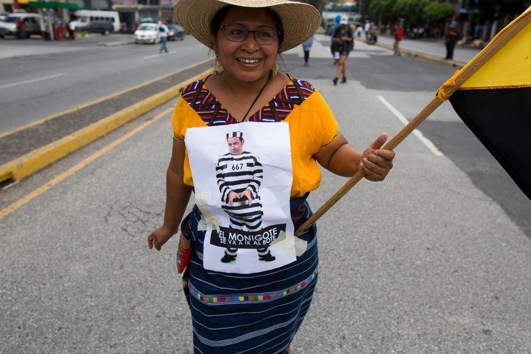 Een vrouw met een karikatuur van de Guatemalteekse president Jimmy Morales in gevangeniskleren.