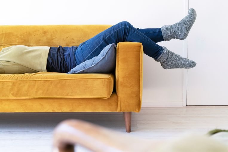 Womans legs on an arm of a couch in a modern livingroom. Beeld Getty Images