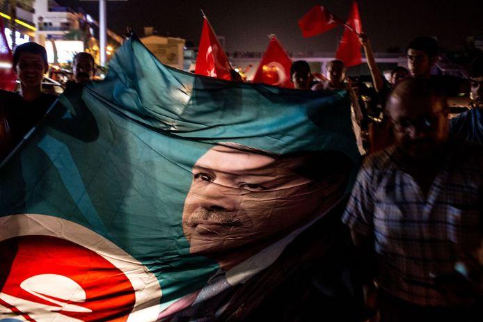Demonstranten laten een vlag zien waarop president Erdogan afgebeeld staat.