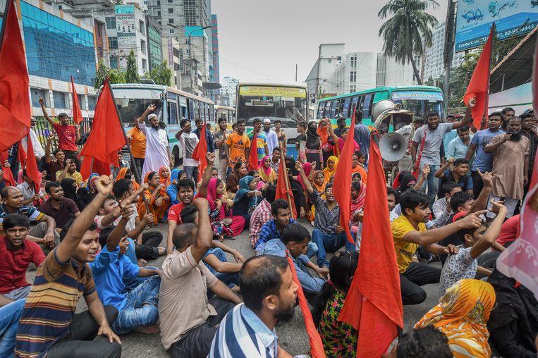 Bengaalse activisten houden een zitactie. De naaiers willen dat Bangladesh een minimumloon invoert.  Beeld AFP