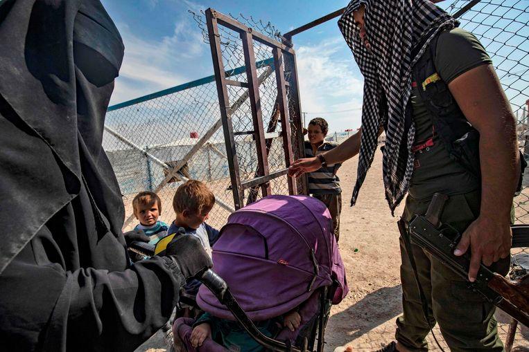 Een bewaker praat met een vrouw en haar kinderen in het kamp Al Hol.  Beeld AFP