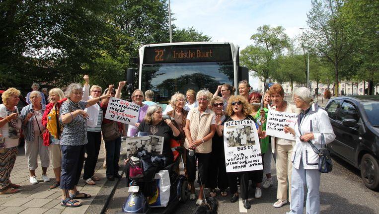 Buurtbewoners protesteren met hun borden voor de lijnbus. Beeld Het Parool
