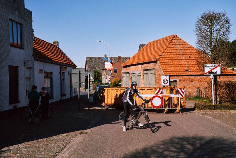 In de gemeente Hoogstraten moet een fietser rechtsomkeer maken voor een container. De grens met Nederland is dicht.  Beeld Thomas Sweertvaegher