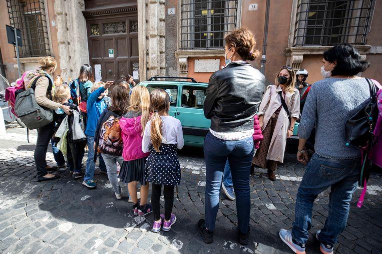 Kinderen wachten voor een basisschool in Rome.  Beeld EPA