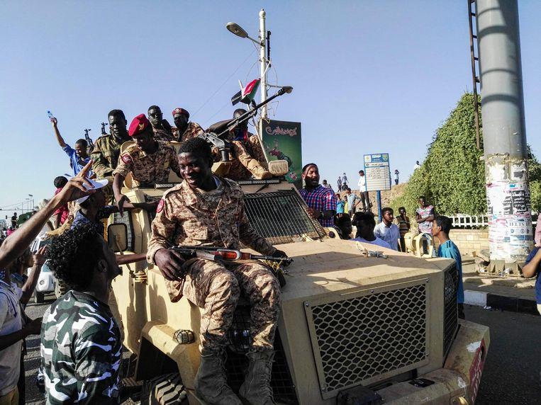 Soedanese demonstranten op een militair voertuig vlakbij het militaire hoofdkwartier van de hoofdstad Khartoem. Beeld AFP