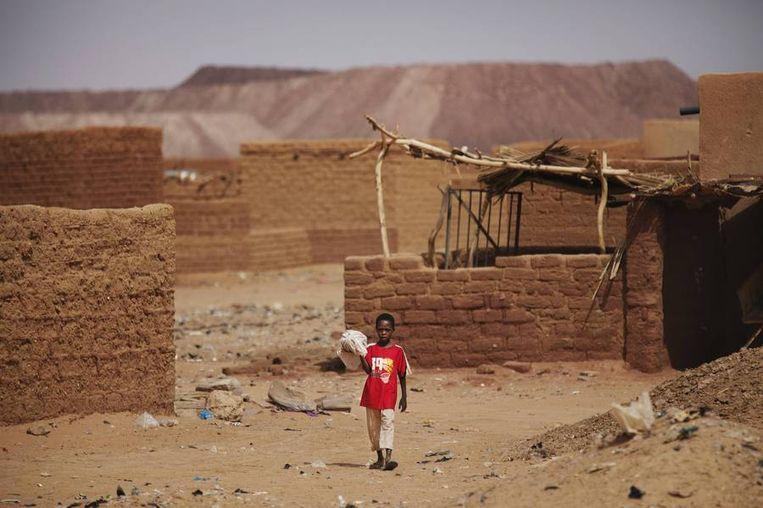 Een jongetje loopt langs lemen huizen bij de mijnen.<br /><br />De stad Arlit in Niger is nog niet veel beter geworden van de lucratieve mijnenindustrie daar. Arlit werd in 1969 opgericht na de vondst van uranium, waarna Frankrijk er de mijnenindustrie ontwikkelde. Nu zijn er twee grote uraniummijnen, in Arlit - waar inmiddels zo'n 117.000 mensen wonen - en in het nabijgelegen Akouta.<br /><br />Maar de inwoners van Arlit zelf zijn daar niet veel rijker van geworden. Hun stad, gelegen tussen het Aïr-gebergte en de Sahara, is stoffig en verwaarloosd. Bovendien zijn er, volgens een rapport van Greenpeace, nog steeds te hoge radioactieve stralingen nabij de Nigeriaanse mijnen. Beeld reuters